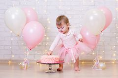 Birthday celebration - funny little girl smashing cake over bric Stock Image
