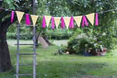 Birthday celebration in garden. Flags decorated garden, ladder by tree, birthday party Royalty Free Stock Photos