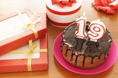 Birthday celebration at nineteen years. A cake with burning candles in the form of numbers and a lot of gifts on a table royalty free stock photos