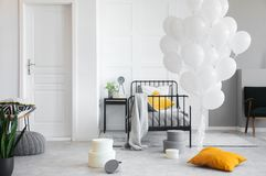 Birthday celebration in white industrial bedroom with metal bed and concrete floor. Concept photo royalty free stock photos