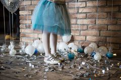 Birthday of the child. A baby girl in silvery sneakers and a sumptuous tulle skirt. On the floor are small balloons.  Royalty Free Stock Images