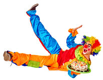 Birthday child clown with cake lying on floor thumb up. Birthday child clown with cake lying on floor and thumb up on isolated. Kid holiday sweet food Royalty Free Stock Image