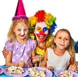 Birthday child clown eating cake with boy together. Kid with messy face. Stock Images