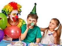 Birthday child clown eating cake with boy together. Kid with messy face. Birthday children clown eating cake with two girl together. Kids with messy face have royalty free stock photos