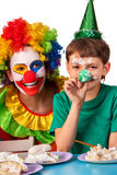 Birthday child clown eating cake with boy together. Kid with messy face. stock photo