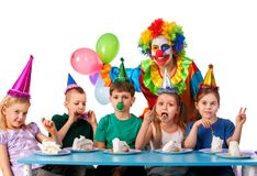Birthday child clown playing with children. Kid holiday cakes celebratory. Birthday child clown playing with children who eat cake. Fun of group people pose for stock photos