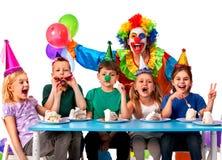 Birthday child clown playing with children. Kid holiday cakes celebratory. Birthday child clown playing with children who eat cake. Kid with nose bunny fingers Stock Photo
