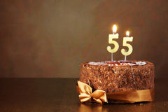 Birthday chocolate cake with burning candles as number fifty five Stock Photography
