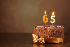 Birthday chocolate cake with burning candles as number sixty five Royalty Free Stock Photo