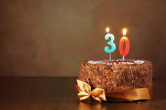 Birthday chocolate cake with burning candles as a number thirty Stock Photo