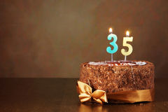 Birthday chocolate cake with burning candles as number thirty five. Birthday chocolate cake with burning candles as a number thirty five on brown background royalty free stock photography