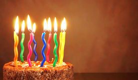 Birthday chocolate cake with burning multicolored candles Stock Photos