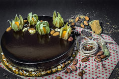 Birthday chocolate mousse cake. With decoration, cocoa beans, almonds, anise and sugar, two spoons and thread on a black background and craft paper with red Royalty Free Stock Image