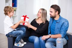 Birthday or christmas concept - couple giving gift to little son. Birthday or christmas concept - young couple giving gift to little son Royalty Free Stock Image
