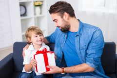 Birthday or christmas concept - father giving gift to his happy. Birthday or christmas concept - young father giving gift to his happy son Stock Photo