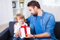 Birthday or christmas concept - father giving gift to his son. Birthday or christmas concept - father giving gift to his little son Royalty Free Stock Images