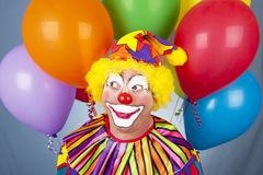 Birthday Clown. Adorable friendly birthday clown surrounded by colorful balloons royalty free stock photography