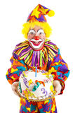 Birthday Clown With Cake. Colorful clown holding a birthday cake. Isolated on white royalty free stock photo