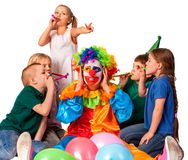 Birthday clown close ears of children`s noise with group children. Birthday clown to close ears of children`s noise. Girl does rabbit ears gesture. Group royalty free stock images