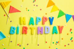 Birthday concept - candles with letters `happy birthday` and confetti. Bright yellow background, top view royalty free stock photos