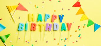 Birthday concept - candles with letters `happy birthday` and confetti. Bright yellow background, top view royalty free stock photo