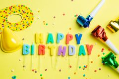 Birthday concept - candles with letters `happy birthday` and confetti. Bright yellow background, top view stock images