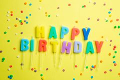 Birthday concept - candles with letters `happy birthday` and confetti. Bright yellow background, top view stock image