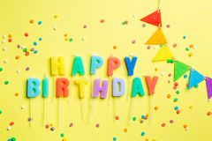 Birthday concept - candles with letters `happy birthday` and confetti. Bright yellow background, top view royalty free stock images