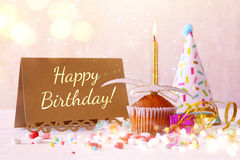 Birthday concept with cupcake and candle next to greeting card Stock Images