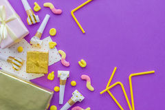 Birthday concept with gifts, greeting cards and party whistles on violet background top view copyspace Royalty Free Stock Images