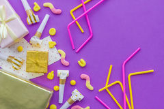 Birthday concept with gifts, greeting cards and party whistles on violet background top view copyspace Royalty Free Stock Photo