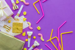 Birthday concept with gifts, greeting cards and party whistles on violet background top view copyspace Royalty Free Stock Photography