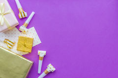 Birthday concept with gifts, greeting cards and party whistles on violet background top view copyspace Stock Photos
