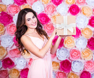 Birthday concept - happy young beautiful woman with gift box ove. Birthday concept - happy young beautiful woman with gift box standing over colorful flowers Royalty Free Stock Photos
