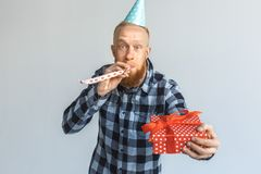 Birthday Concept. Mature man in cap standing isolated on grey giving gift to camera blowing party horn cheerful stock photo