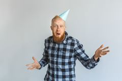 Birthday Concept. Mature man in cap standing isolated on grey hands aside looking camera surprised stock photos