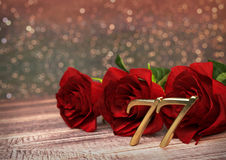 Birthday concept with red roses on wooden desk. seventy-seventh. 77th. 3D render. Birthday concept with red roses on wooden desk. 3D render - seventy-seventh Royalty Free Stock Photography