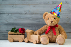 Birthday concept, teddy bear in party cap and wooden toy train. Grey wooden background Royalty Free Stock Photo