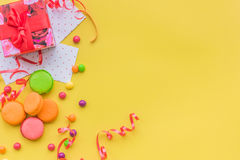 Birthday concept with wrapped gift and sweets on yellow background top view copyspace Stock Photo
