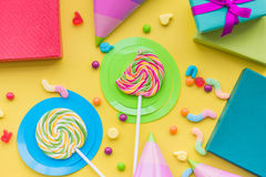 Birthday concept with wrapped gifts, greeting cards and sweets on yellow background top view Stock Image