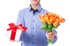 Birthday concept - young man with flowers and gift box isolated Stock Photos