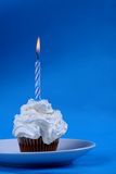 Birthday cupcake. With a single candle on it on blue background Royalty Free Stock Photography