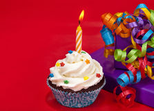 Birthday Cupcake. A birthday cupcake with colorful sprinkles on a red background with presents and ribbon royalty free stock images