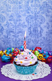 Birthday Cupcake. A cute birthday cupcake on a purple background with a lit candle. Make a wish stock photos