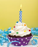 Birthday Cupcake. A birthday cup cake with vanilla icing, sprinkles and a lit birthday candle. Make a wish stock photo