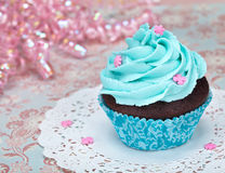 Birthday Cupcake. A birthday cup cake with blue icing and pink sprinkles stock images