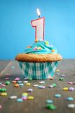 Birthday cupcake. Number one birthday candle on a blue cupcake on blue background Stock Photo