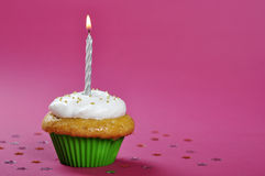 Birthday cupcake. With whipped cream and candle on pink background Stock Image