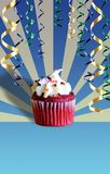 Birthday Cupcake. Pink cupcake with icing and sprinkles on a blue background with colored streamers royalty free stock image