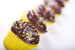 Birthday Cupcake. Row of Birthday Cupcakes with Sprinkles and Chocolate Icing royalty free stock image